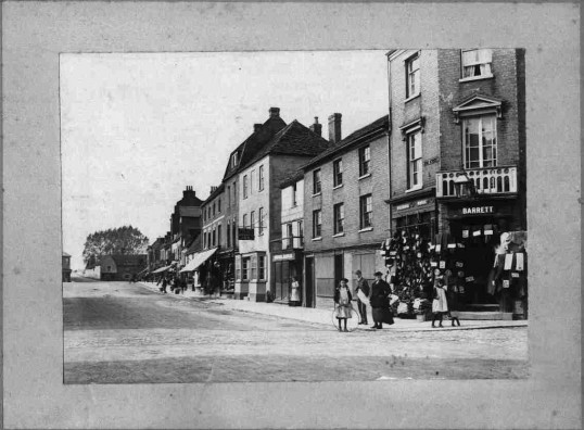 Market Square, St Neots, from the east showing the north side from Barrett's corner to the Bridge & Half Moon Hotel,  child in foreground with hoop. about 1900