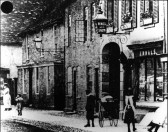 Children standing outside the Royal Oak and the adjacent cottage, Ennals shop window at right, in St Neots High Street, about 1880.
