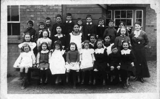 Hail Weston School, a group of children with a female teacher. School building at background. 1916.