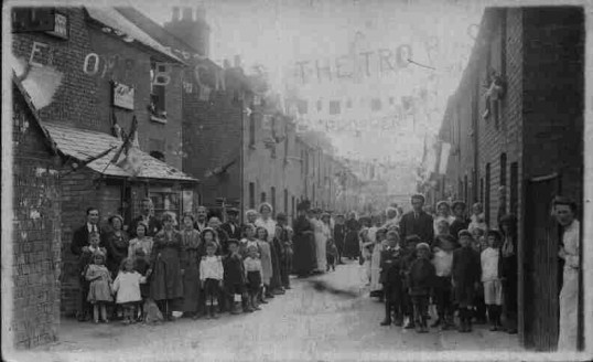 St Neots.Russell Street decorated for celebrations at WW1 armistice with large crowd. Banner 'Welcome Home to the Troops' 1918