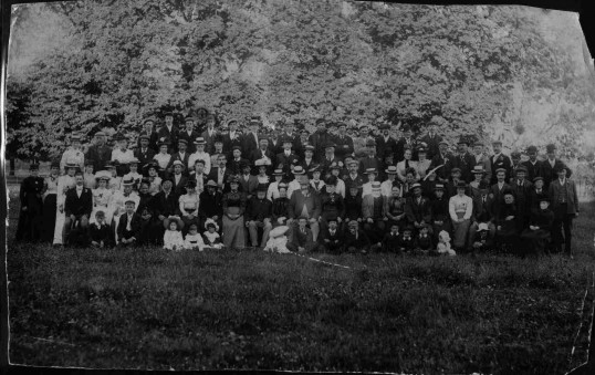 Monochrome group photograph of staff of G.F. Rowley, Priory Hill, St. Neots with their families. 9th August 1902 celebrating the coronation.