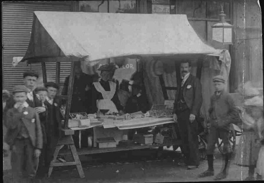 Small stall St. Neots Mkt Square - selling sweets & biscuits with scales, about 1900.