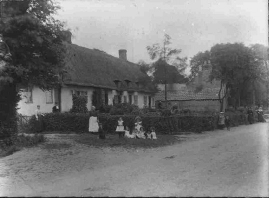 Children in front of thatched cottages, a barn & house in Staploe (date unknown)