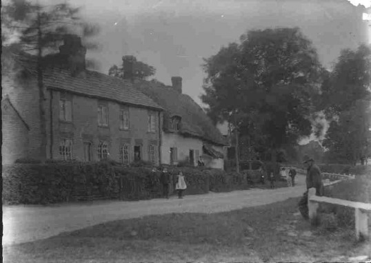 Villagers standing outside brick built houses and a thatched cottage, in Brookside, Staploe, c1910