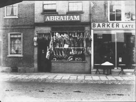 St. Neots High St,  Sam Abraham in his butchers shop & Barkers Furniture Shop next door, about 1900. Note the cobbled pavement.