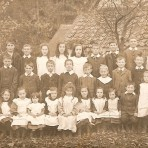 School photo Upwood School.  Standing in front of cottages since demolished.  Early 2oth century.