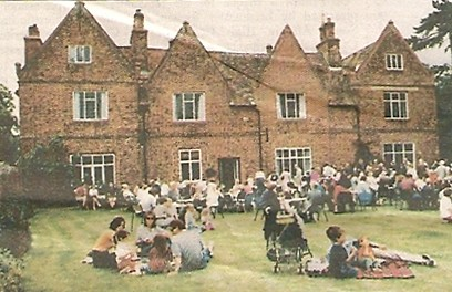 A crowd of people enjoying a strawberry tea in the old Manor gardens Wilburton