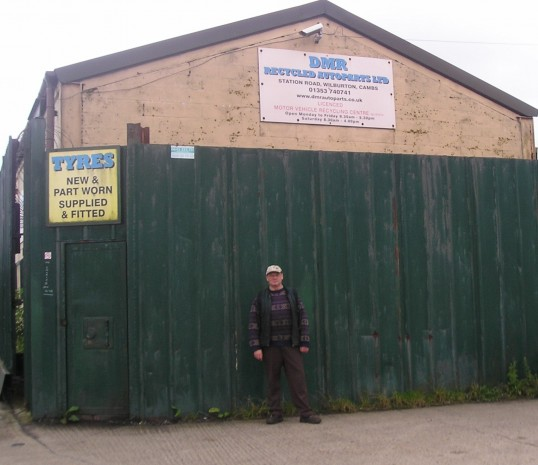Mr R Northcote in front of the D.M.R. Recycle & scrap yard in Grunty Fen, Wilburton