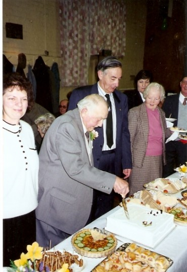 Mr George Yarrow cutting his birthday cake on his 90th birthday