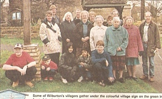 Wilburton villagers gather under the village sign on the church green