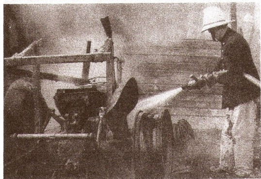 Fireman dowsing a tractor at Mr Layton's farm fire
