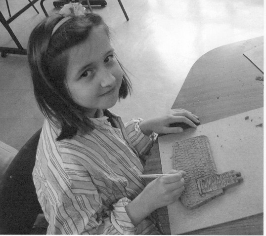 A member of the school group making a roof for one of the houses on the plaque