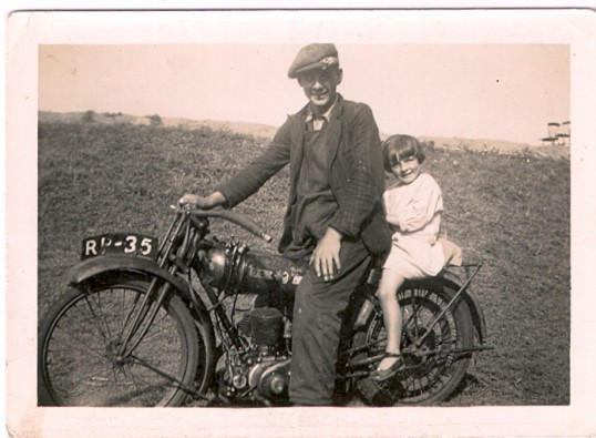 A photo of Pearl Day on her brother's motor cycle on the river bank Wilburton