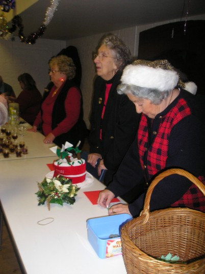 Three of the St Peter's club committee serving wine to guests & members as they arrive for there xmas lunch