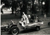 Harold Sharp driving a tractor in a Wilburton feast parade & Mr Harris standing at the side