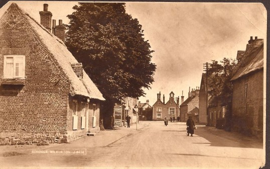 Wilburton High Street with the old blacksmith's cottage on the left & the school in the distance