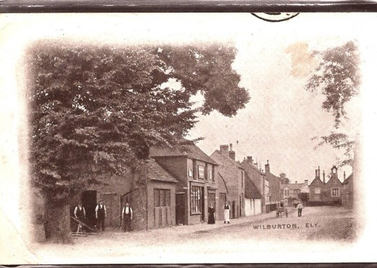 Wilburton, High Street with the blacksmith's shop and 3 of the workers in the foreground also the old grocery shop