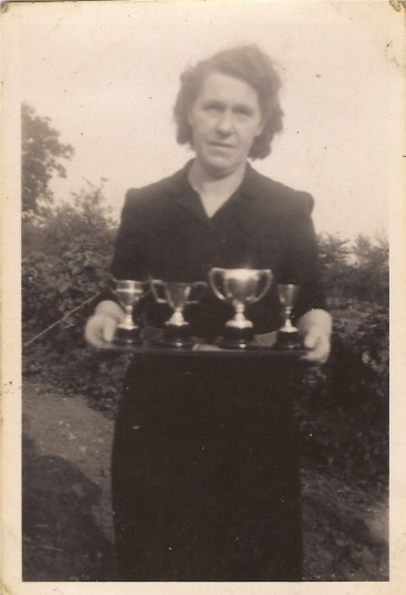 Mrs Edgley holding silver cups that Gordon (Pop) Day won when he was boxing