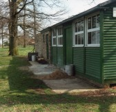 Front of the old pavilion with the toilet block. New tool shed construction at Wilburton.