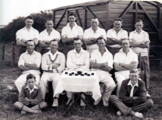 Cricket Club Group photo with trophies in front of 'pavilion' ( old railway carriage)