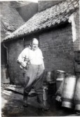 Percy Giddens at rear of White Horse standing by his milk churns which were used for his milk business that he ran from the White Horse.
