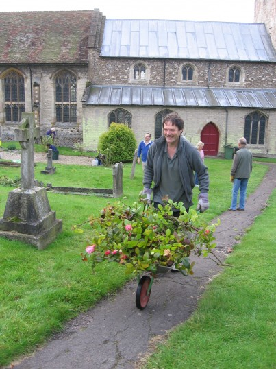 Clive Pickton, with barrow, and others, gardening at St
